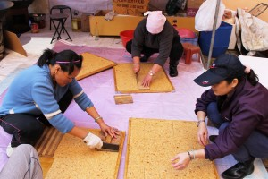 婦女們把米通切成一小塊,放進包裝袋,派送給親友。