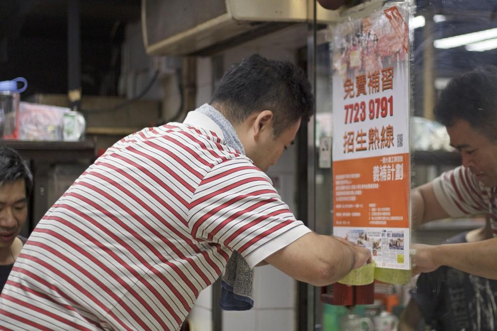 訪問期間,義工在明哥的餐廳內忙於張貼有關免費補習的海報。