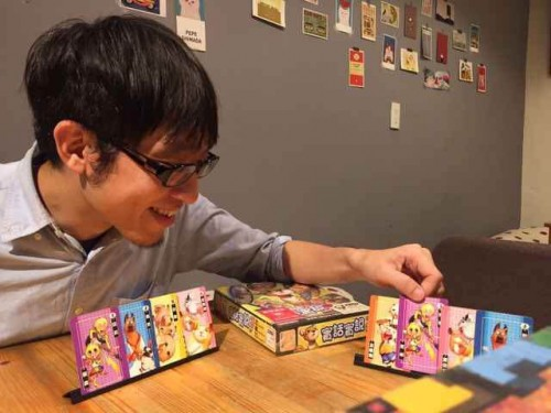 桌遊設計師龔義詔在介紹 新的桌上遊戲。(受訪者提供)