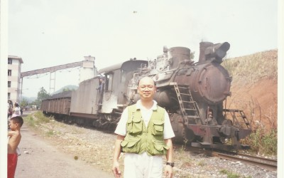 Yam in front of a narrow-gauge steam engine in Hunan, China